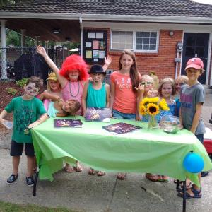 Olivia (in the red hat) and Claire (third from left, in the blue bathing suit) hosted a neighbourhood party and calendar sales event.