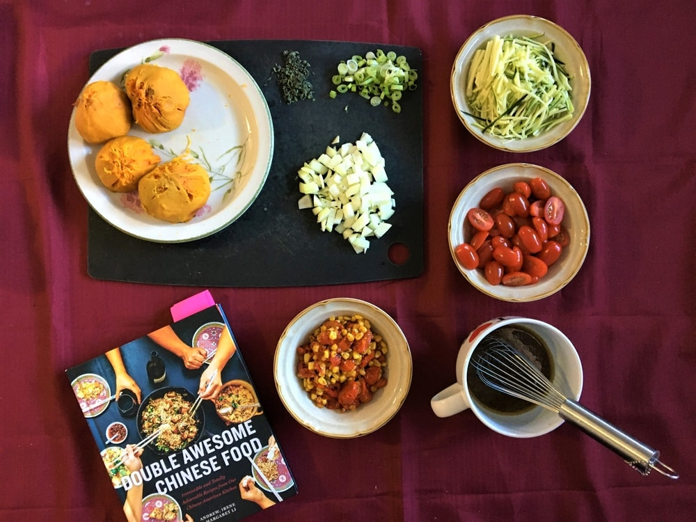 Bowls of prepared ingredients and the cookbook cover arranged on a black cutting board and red tablecloth