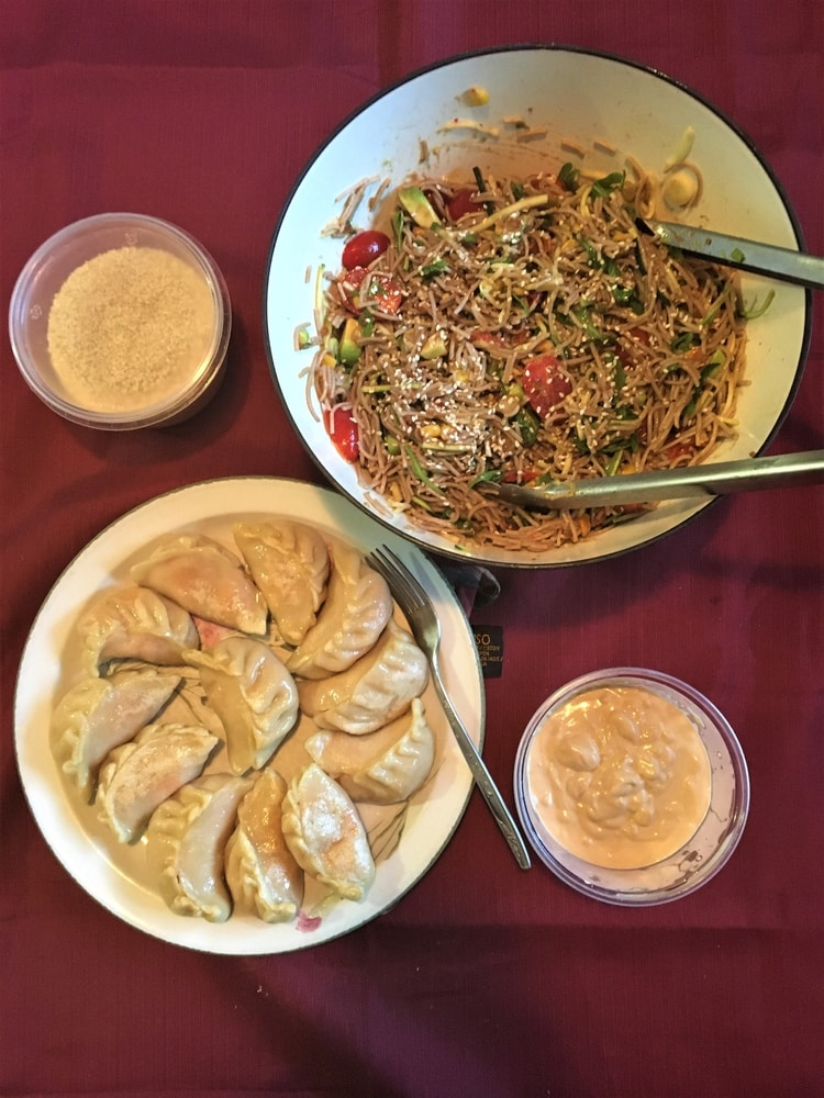 A plate of dumplings, and bowls of salad, dip and sesame seeds on a red tablecloth