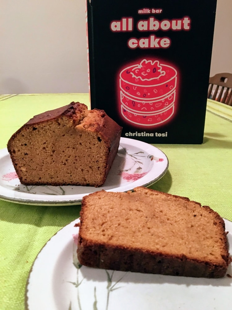 A plate with a slice of pound cake in the foreground with the remaining cake on a plate and a cookbook behind it.