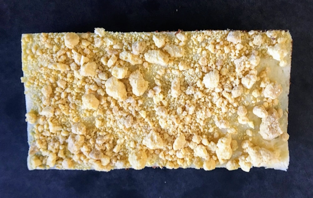A cake topped with yellow crumbs on a scuffed black cutting board.