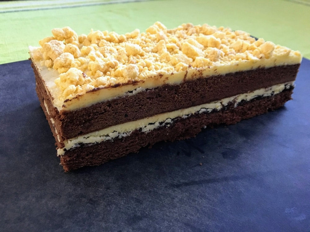 A large chocolate cake with two layers of yellow frosting and crumbs on a scuffed black cutting board.
