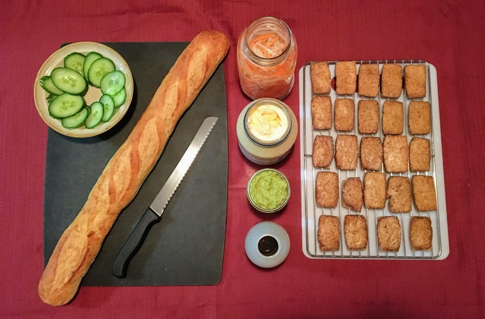 An overhead shot of a cutting board and wire rack covered with a baguette, cucumbers, jars of sauces, pickled vegetables and baked tofu.