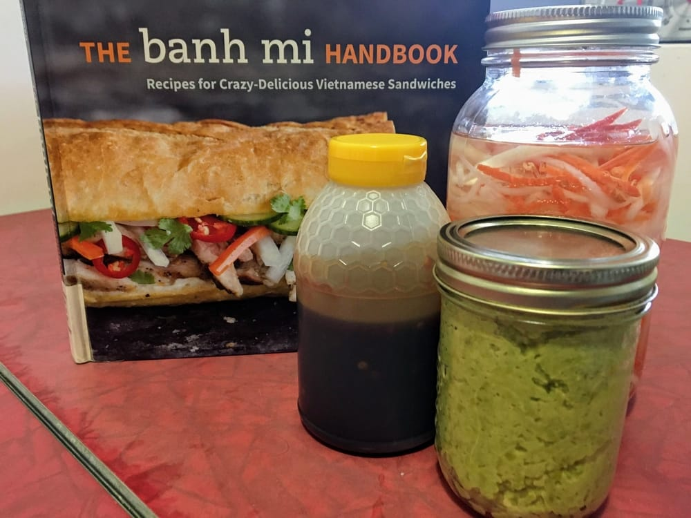A jar of green edamame pate, spicy hoisin sauce and pickled carrot and daikon, in front of a cookbook cover.