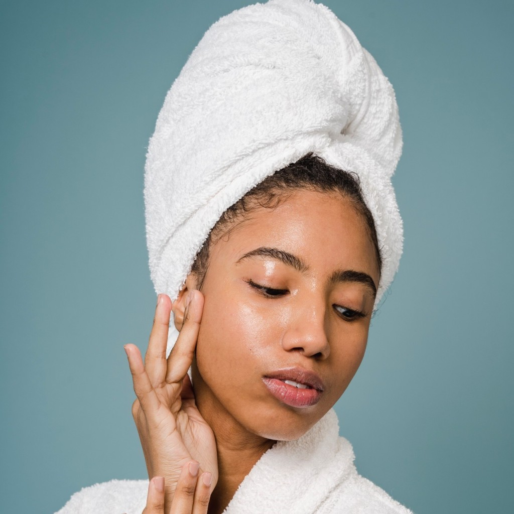 A close up of a person touching their face and showing off the glow of their skin while wearing a bathrobe and towel on their head.