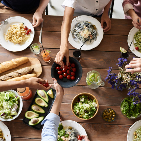 A table set with plates of food and ingredients in bowls including cherry tomatoes, olives, avocados, bread, and small purple and white flowers in a vase. Hands reach out across the table to take ingredients from the bowls.
