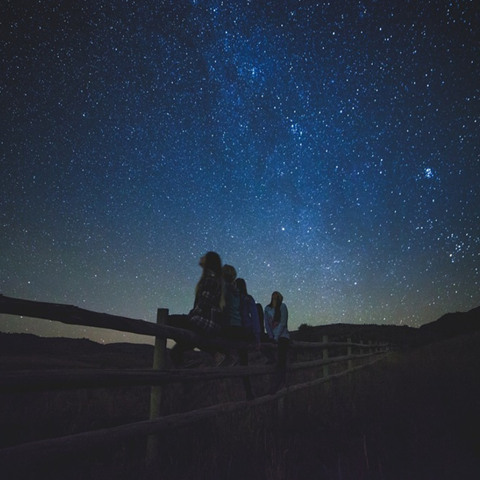 Four people are sitting on a wooden fence in the middle of a field. It is nighttime and they are looking up at a sky full of stars.