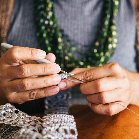 A person is crocheting with silver yarn. They are wearing a knitted green scarf and their hands are in focus.