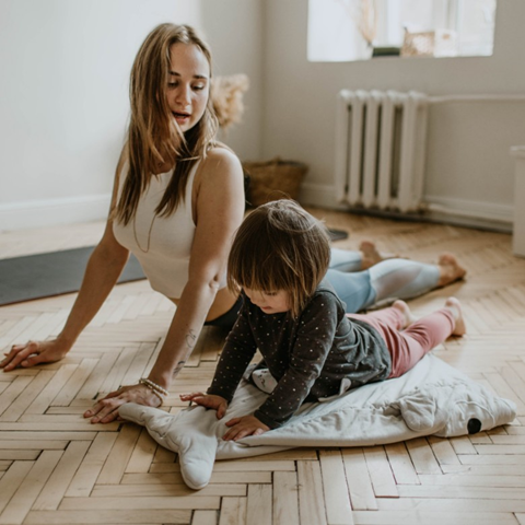 An adult and a child both do the downward dog yoga pose in a small indoor space.