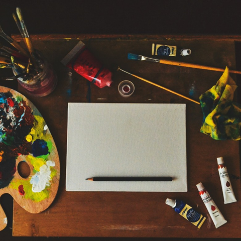 A blank sheet of paper sits on a desk surrounded by an easel, tubes of paint, paintbrushes in a glass jar, and a rag covered in paint smudges.