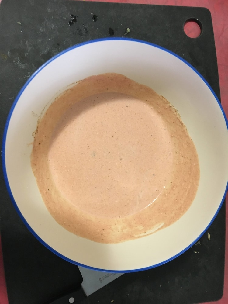 A bowl of speckled, pale orange sauce that looks very unappetizing.