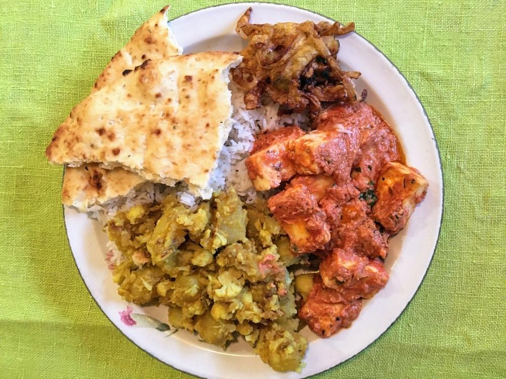 A plate with aloo gobi, paneer makhani, onion bhaji, rice and pita bread on a green tablecloth.