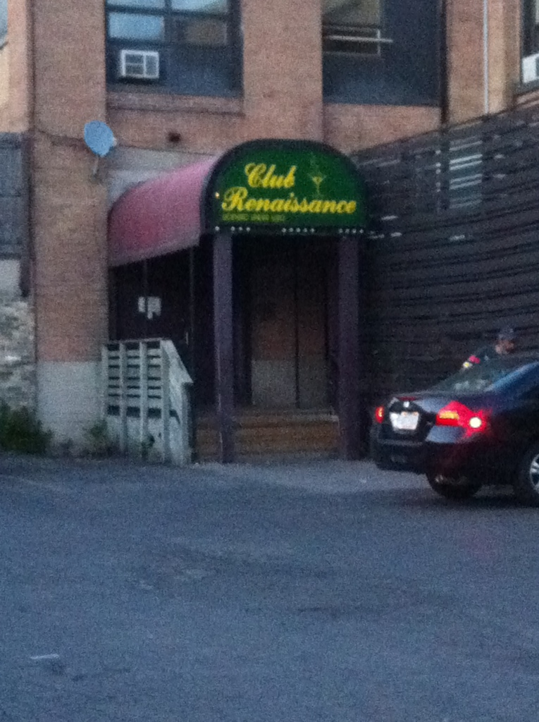 A photo of the entrance of Club Renaissance. Taken from the parking lot, a green sign has yellow writing on it reading Club Renaissance, and has an image of a martini with bubbles rising up from it.