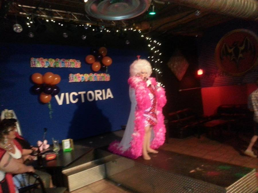 A photo of the inside of Club Renaissance. Drag queen Victoria Parks performs in a robe trimmed with a huge amount of pink feathers, a sparkly patterned dress and a fluffy white wig. Behind her at the back of the stage are banners that read Happy Birthday Victoria.