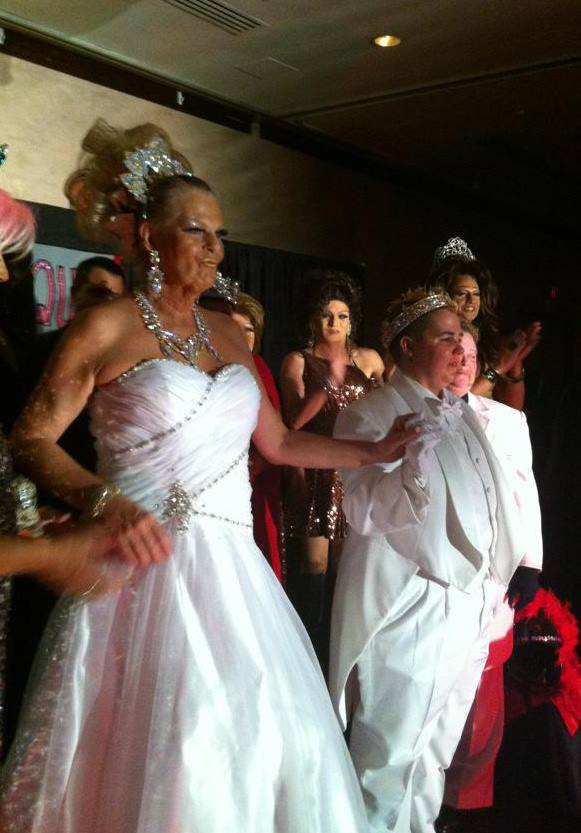 Late drag queen Robin Derring performs on stage in a gorgeous white gown, diamond jewelry, and a sky high blonde updo. Beside her is a drag kind in an all white tux and tails wearing a crown. Multiple drag performers stand behind them clapping.