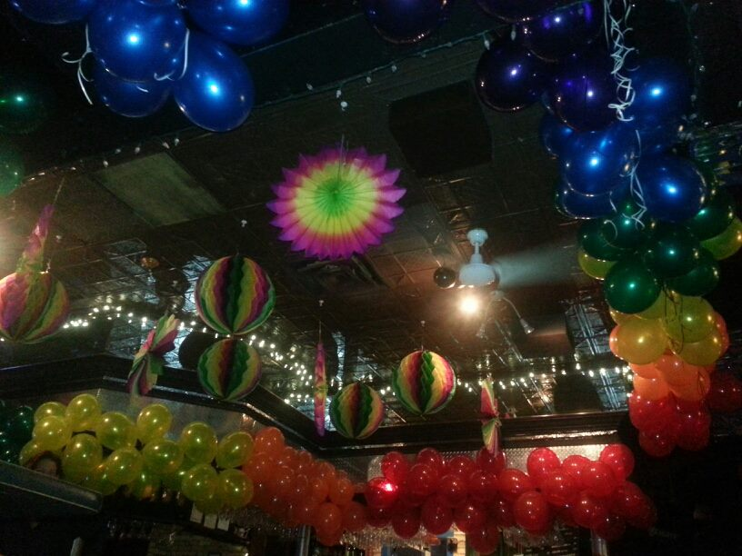 A photo of the ceiling around the bar at Club Renaissance. Surrounding the bar are balloons arranged by colour into a rainbow and from the ceiling hang multi-coloured paper decorations.