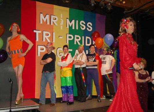 """A photo from inside Club Renaissance. Miss Drew presides over the Mr and Miss TriPride pageant in a red gown and hairpiece. Seven drag kings and queens post on the stage in front of a large rainbow banner that reads """"Mr and Miss TriPride Pageant""""."""