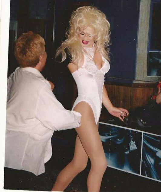 A photo of the gorgeous drag queen Miss Drew wearing a white lace bustier, red lipstick and a bouncy blonde wig. A woman with short blonde hair and a white dress shirt is dancing with her.