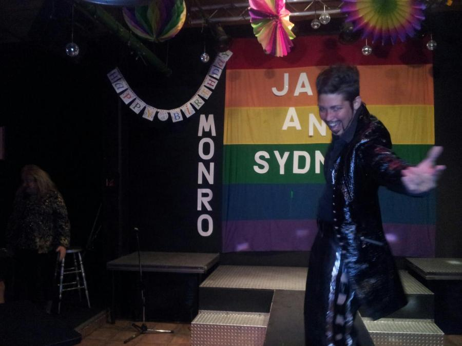A photo of the stage and runway at Club Renaissance. A drag king in all black with a long coat and a goatee reaches out his hand to the audience. Behind him a pride flag hangs with the name Jay and Sydney. There are decorations hanging from the ceiling and beside the flag there is a banner that reads Happy Birthday and the name Monro.