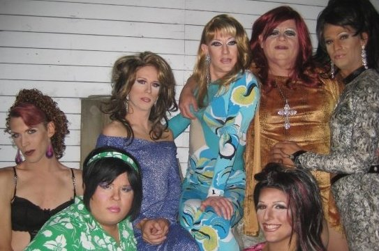 A photo of seven gorgeous drag queens posing together in full makeup, hair and outfits.