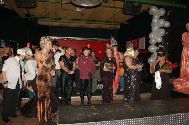 A photo of the inside of Club Renaissance during a drag pageant. Many drag queens and kings are standing beside the stage and runway wearing crowns. Miss Drew presides over the ceremonies with a microphone.