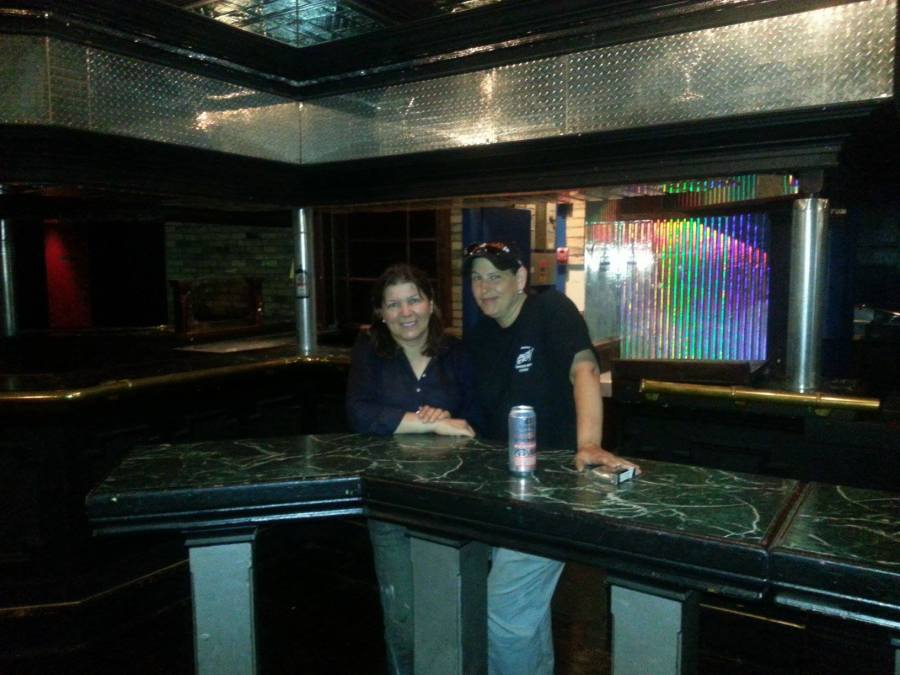 A photo inside of Club Renaissance after it has closed. Owners Fran and Cheryl pose for a last photo together at Club Renaissance in front of the bar.