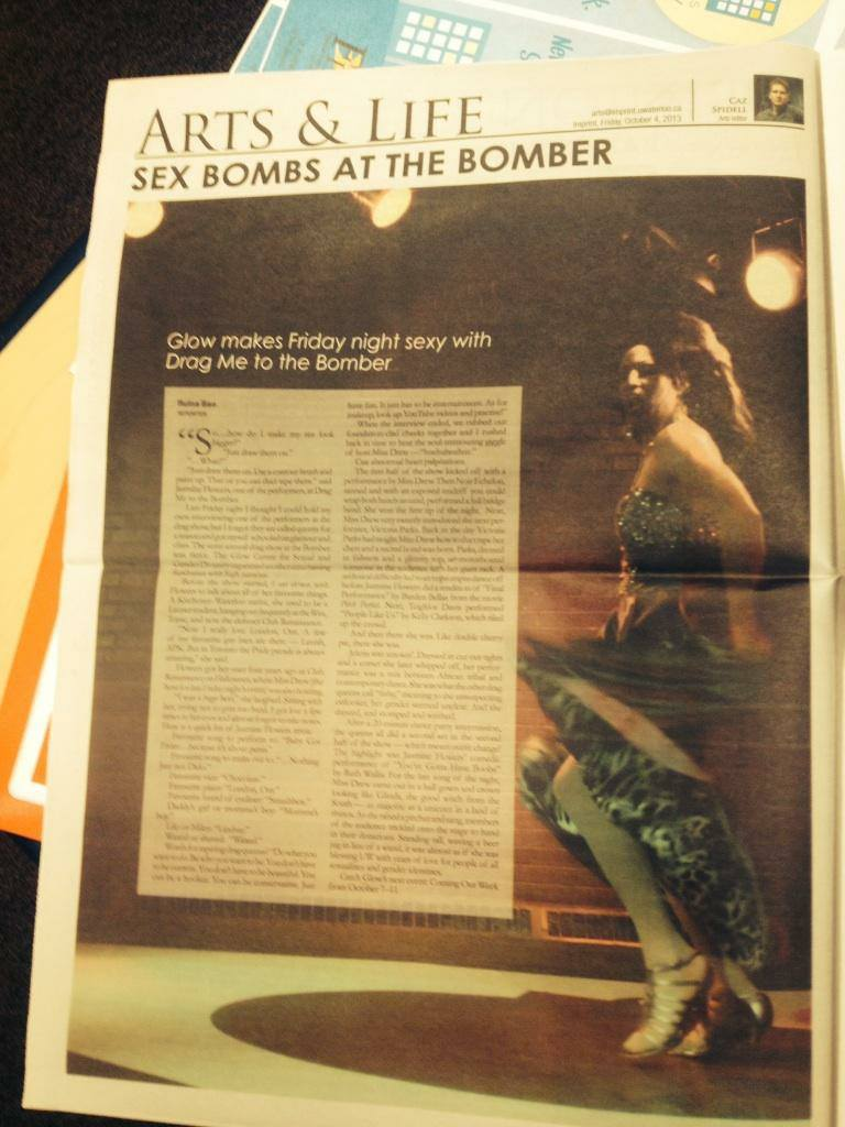 """A photo of a newspaper open to a page with an article about the Drag Me To The Bomber shows held at the University of Waterloo. The headline reads """"Glow makes Friday night sexy with Drag Me To The Bomber"""" and there is a large photo of a drag queen twirling under a spotlight."""