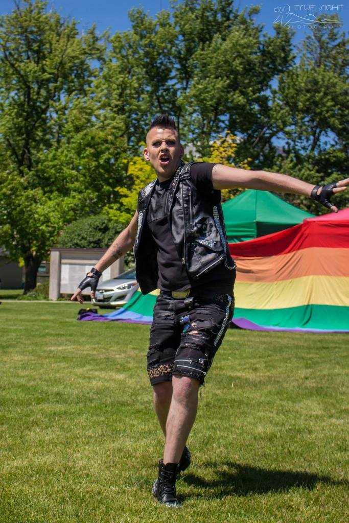 A photo of drag performer Troy Boy Parks performing in Victoria park during TriPride. Troy wears a leather vest and gloves and lip syncs dramatically in a grassy field in front of large pride flags.