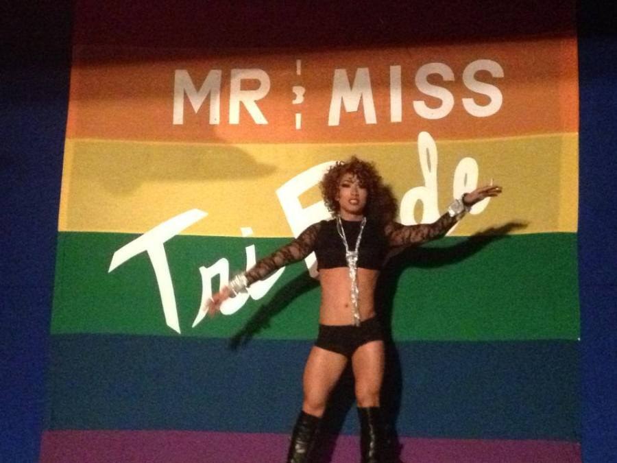 A photo of a drag queen in knee high black leather boots, hot pants, a lacy black shirt, silver jewelry and a short curly wig performs on stage at Club Renaissance during the Mr and Miss TriPride Pageant in 2013.