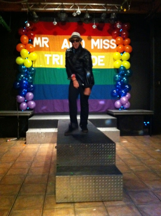 """A photo from inside Club Renaissance. A drag king with a jacket, sunglasses and a fedora dances on stage. Behind him is a rainbow banner, surrounded by rainbow balloons, that reads """"Mr and Miss TriPride"""""""
