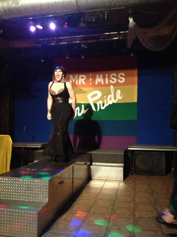A photo from inside Club Renaissance of a drag queen in a black gown lip syncing powerfully to a song. Behind her at the back of the stage is a large rainbow banner that reads Mr and Miss TriPride.