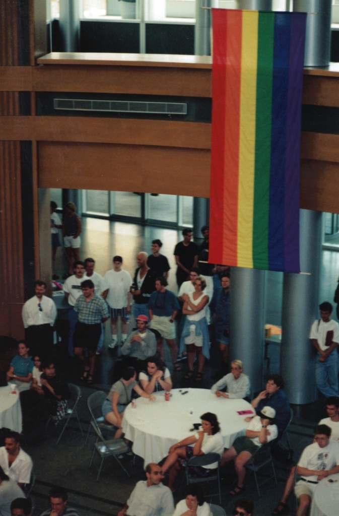 A photo taken from above, looking down at a crowd of people standing and sitting at tables at the Kitchener City Hall rotunda. A large rainbow flag hangs from the ceiling.