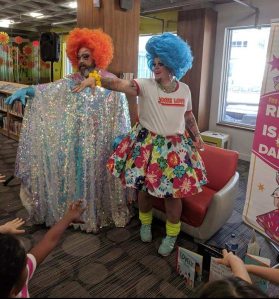A photo from inside Kitchener Public Library showing drag queens Fay and Fluffy performing a song and interactive dance for kids in 2019.