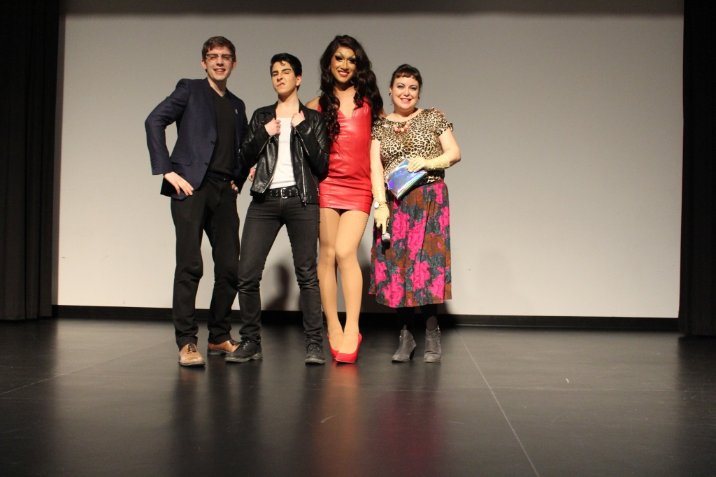 A photo from inside the Kitchener Public Library's theatre. Staff members Curtis Williams and Ellie Anglin pose on stage with drag king George Swooney and drag queen Kyne.