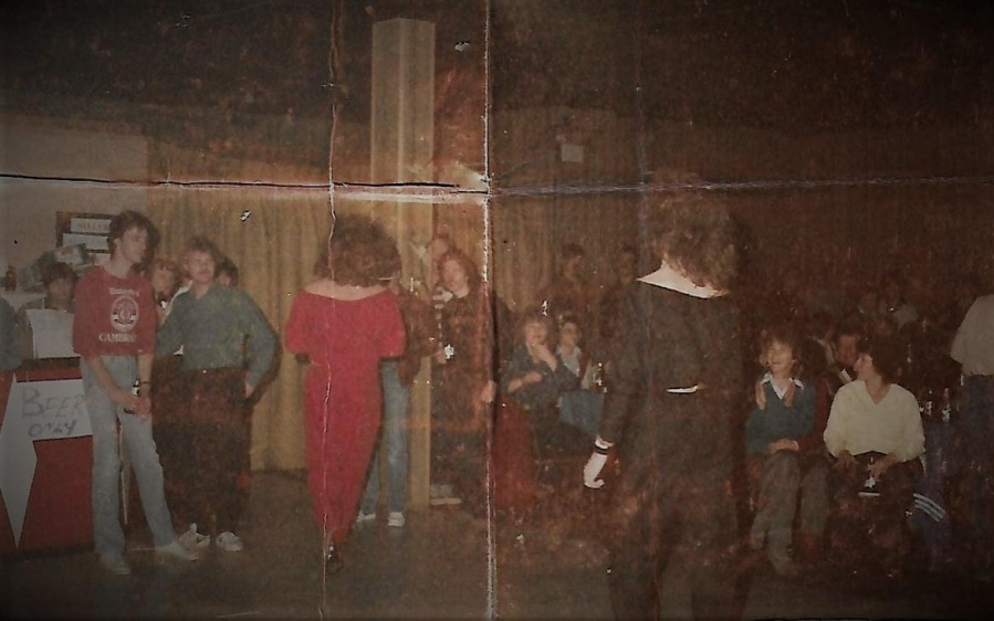 An old photo taken inside The Robin's Nest in the late seventies or early eighties. Two glamorous performers walk the runway as a delighted audience watches.