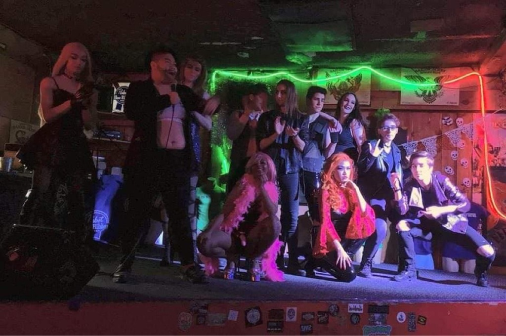 A photo taken from inside The Chainsaw. Eleven drag performers pose on stage as Manny Manila speaks into a microphone.