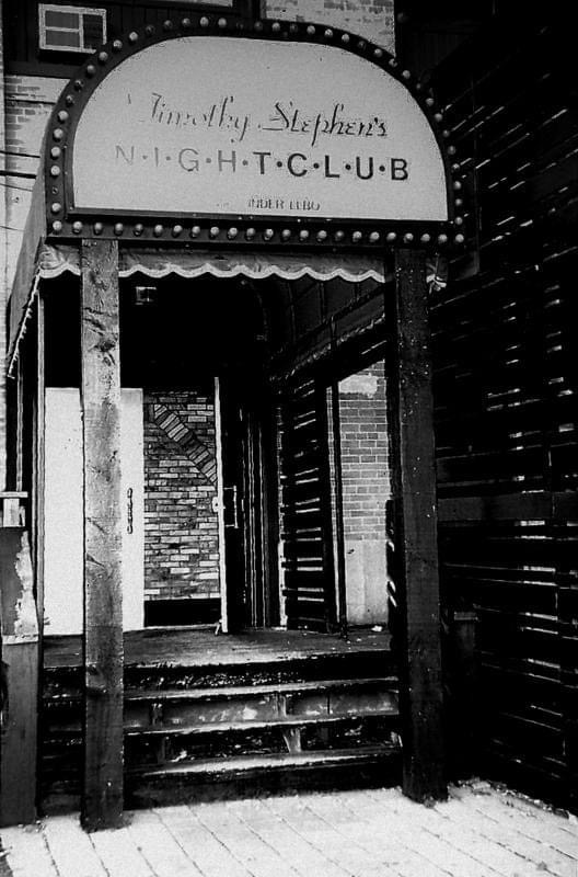 A photo from the outside of Timothy Stephen's Nightclub showing a sign with lights around it above steps entering into the club.